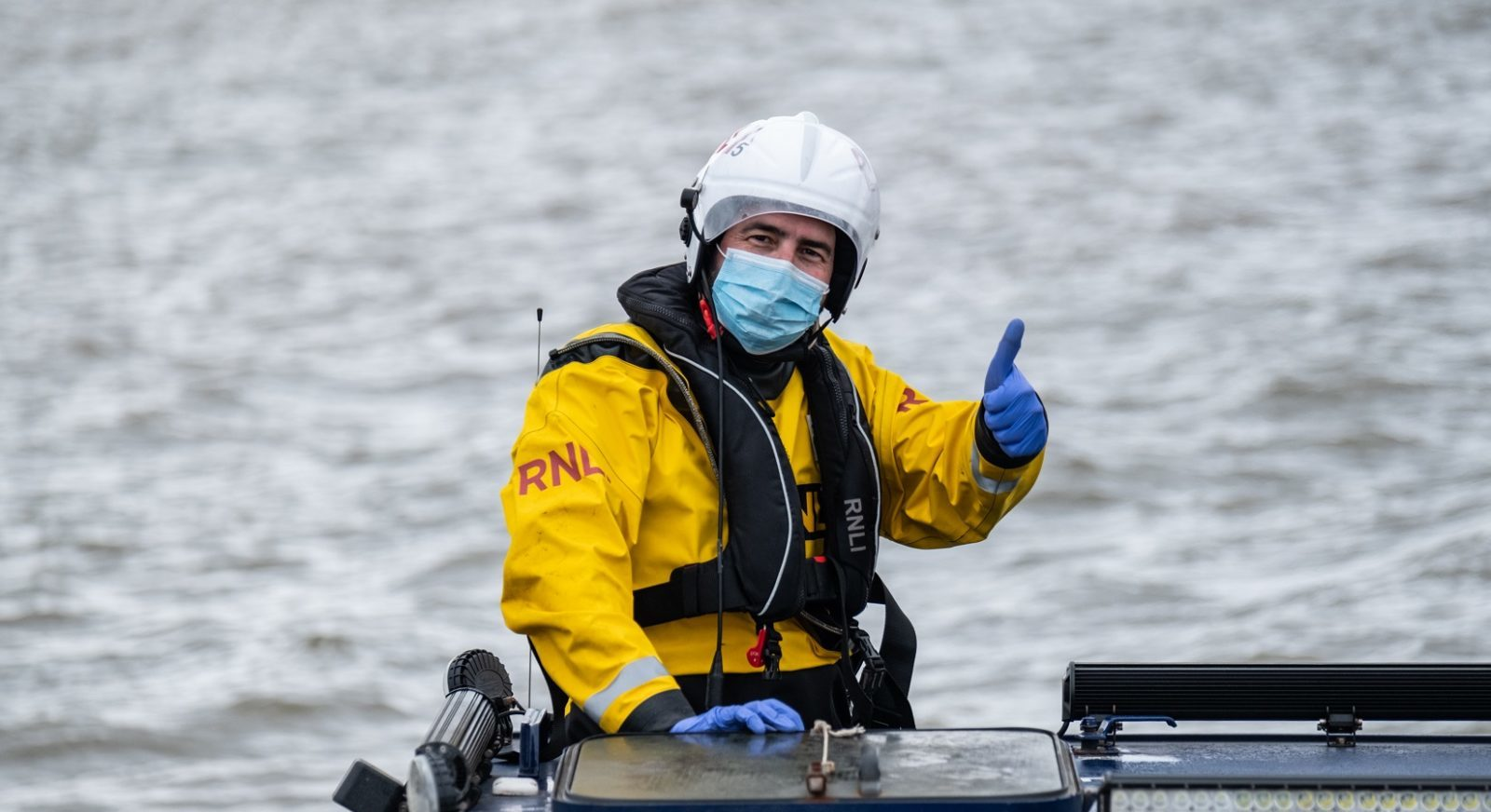 West-Kirby-Crew-Member-Adie-Gregan-who-was-involved-in-Wendys-rescue-wearing-a-face-mask-and-gloves-and-giving-a-thumbs-up-from-the-stations-launching-vehicle